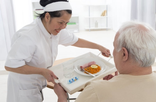 caregiver serving food to an elderly man